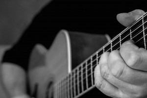 black and white close up photo of a person playing the guitar