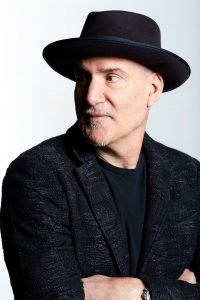 Peter Himmelman wearing a hat and all black in front of a white background.