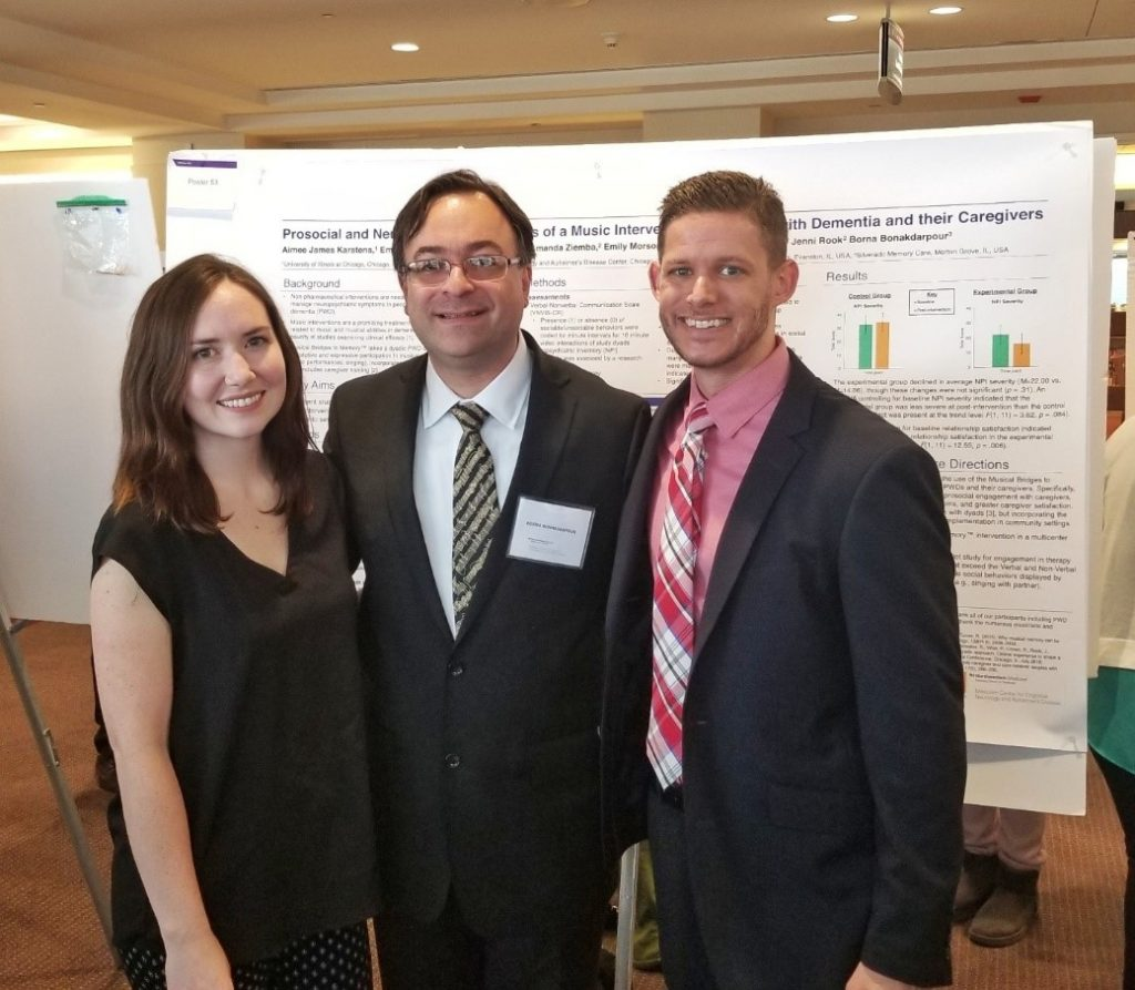 Aimee Karstens, Borna Bonakdarpour, and Jeffrey Wolfe stand smiling in front of the Musical Bridges to Memory research poster