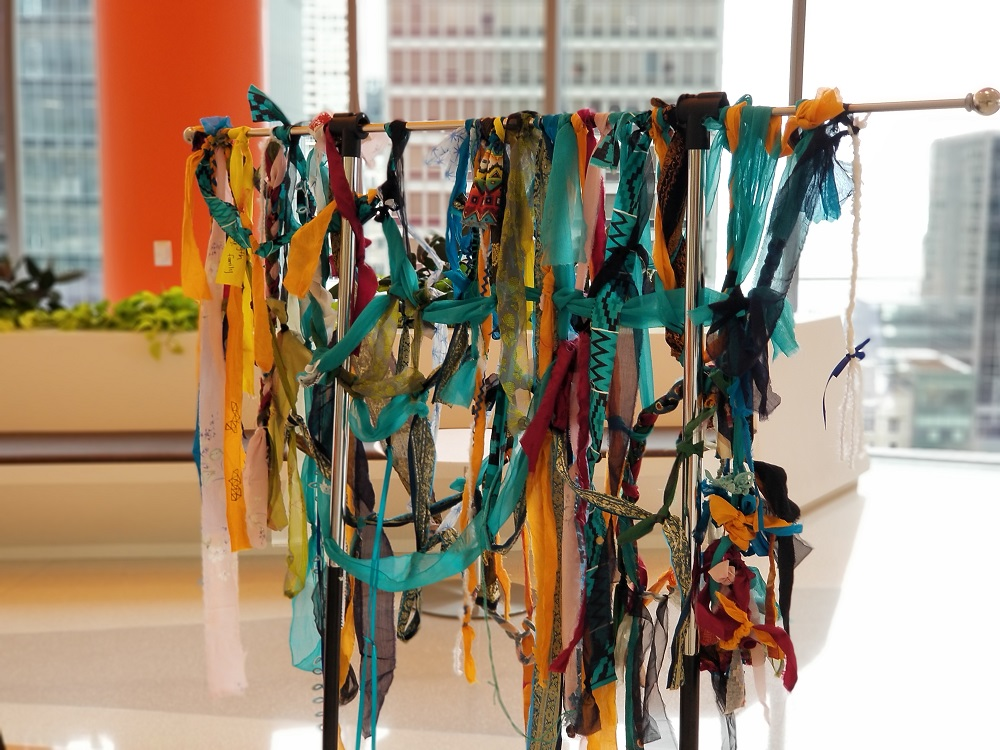 Strips of colorful fabric ied together on a metal rack in a well lit room with large winows in the background