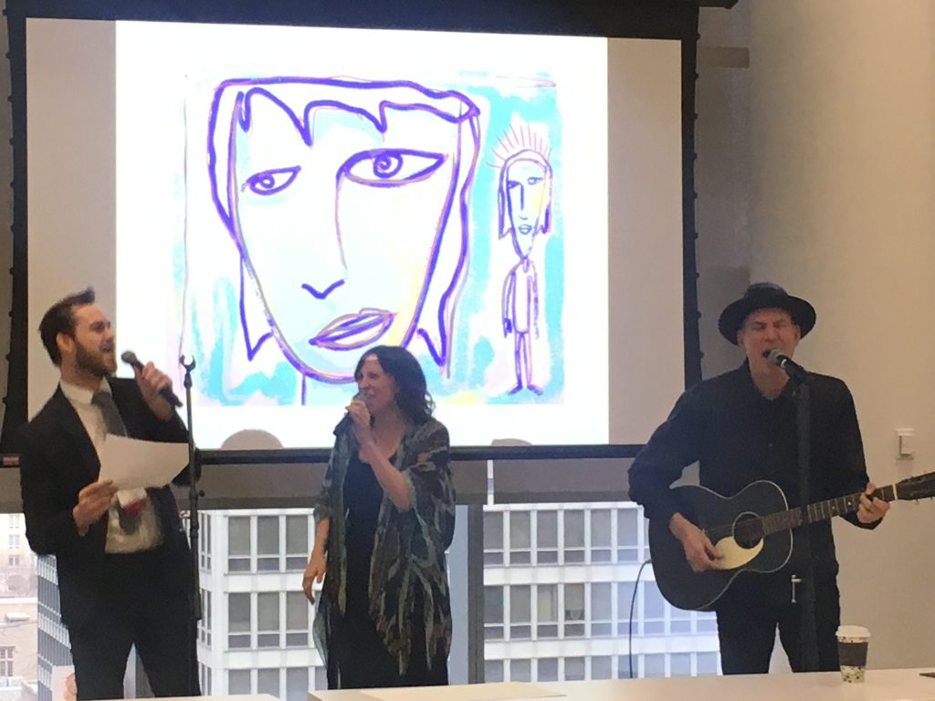 Brad Drowsdowski, a conference attendee, and Peter Himmelman sing while Peter plays a guitar. A powerpoint slide of a cartoon woman is in the background.