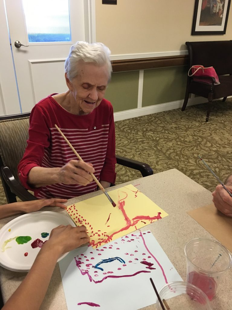 An Auberge community member paints on yellow and white paper with red and pink paint