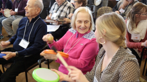 Two MBM participants smiling and playing hand instruments in a room of other MBM participants