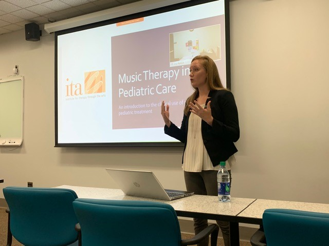 Amanda Ziemba presenting a PowerPoint on Music Therapy in Pediatric Care