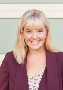 Headshot of Sara Renauer-Reid smiling wearing a maroon blazer