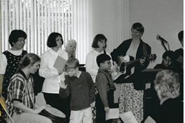 Black and white photo of five adults stood up against a window, one holding a guitar, with one adult sat in front holding a drum. Two children stand in front, one watching the guitar and the other playing the drum.