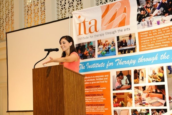 Jenni Rook, Executive Director of ITA, stands behind a wooden lecture podium with a small microphone, smiling and gesturing in front of her. Behind her stands the ITA banner made up of multiple photos with orange and blue writing text of ITA's title.