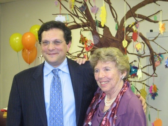 The late Dr. Ted Rubenstein, left, and Marilyn Richman, right. They have their arms around each other, smiling, and are dressed in formal clothing. Behind them are yellow and orange balloons and a Papier-mâché tree with hand-made ornaments hanging from the branches.