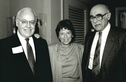 Black and white photo of three people stood together, smiling in formal dress with Toddy Richman in the center.