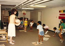 Color photo taken at the Evanston Child Care Center 1990. Marilyn Richman stands banging a hand drum with seven children standing or crouched facing her in a semi-circle. The room has no windows, with fluorescent strip-lights across the ceiling and an indoor basketball hoop.