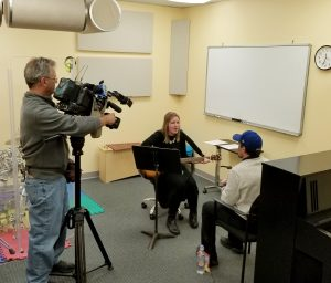ABC 7 cameraman filming a music therapy session. An ITA intern holds a guitar while the client is singing in a chair opposite her.