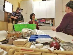a close up of art supplies and musical instruments with Karen Jordan and Marni Rosen talking in the background and a cameraman behind them.