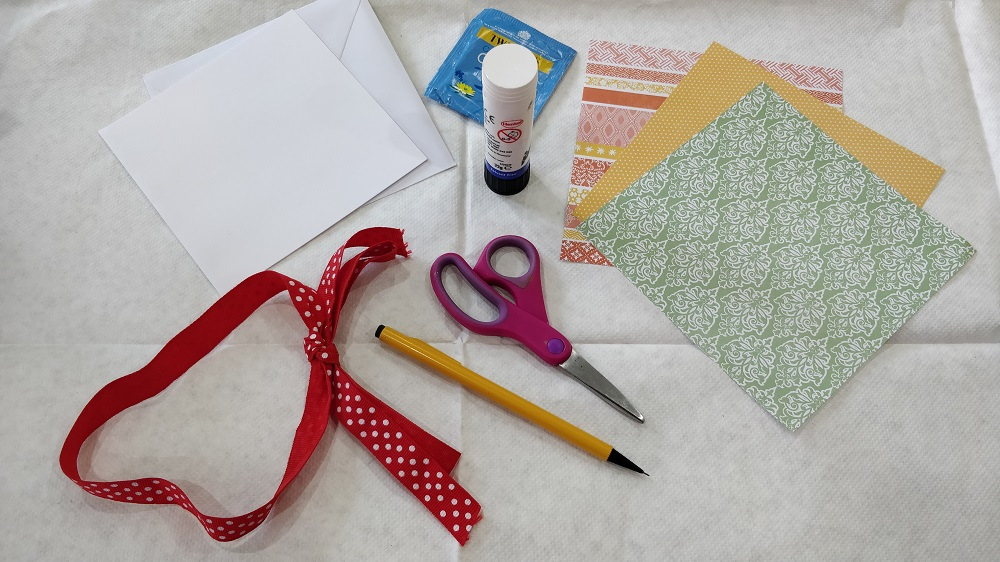 colorful paper, scissors, a pencil, ribbon, a glue stick, a tea bag, a card and envelope sit on white fabric.