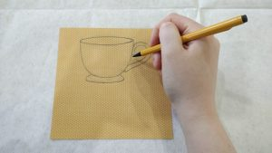 a person draws a teacup on yellow decorative paper with a pencil