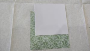 a white card sits on top of a piece of decorative paper