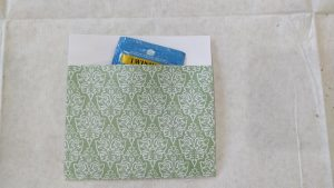 A decorative paper pocket with a tea bag inside