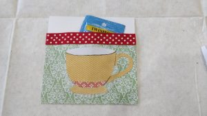 A decorative paper pocket with a paper teacup outside and a bag of tea inside