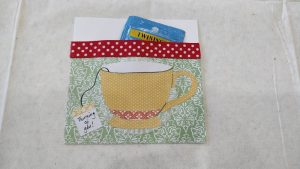 """A decorative paper pocket with a paper teacup on the outside and a teabag tag that reads, """"thinking of you"""". A teabag sits inside the pocket."""