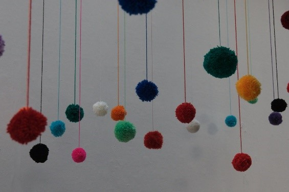 colorful pom poms hanging from long strings