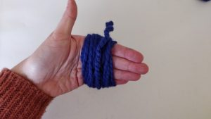purple yarn wrapped around a person's fingers