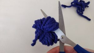 scissors cutting the ends of a lump of yarn apart