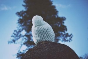 the back of a person's head, they are wearing a beanie with a pom pom and standing in front of a tree.