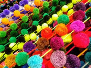 many colorful pom poms on strings