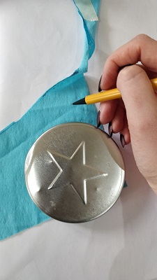 A person uses a metal disc to draw a curved edge onto a piece of blue fabric.