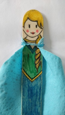 A popsicle stick drawn to look like Queen Elsa from Frozen with a small blue cape fastened with an elastic band around the neck.