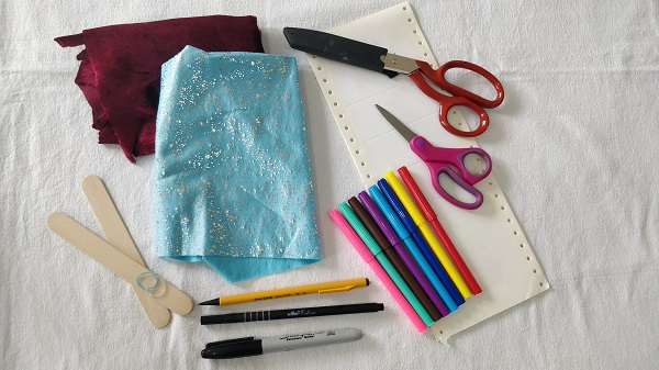 Markers, scissors, fabric, popsicle sticks, and utensils gathered on a table.
