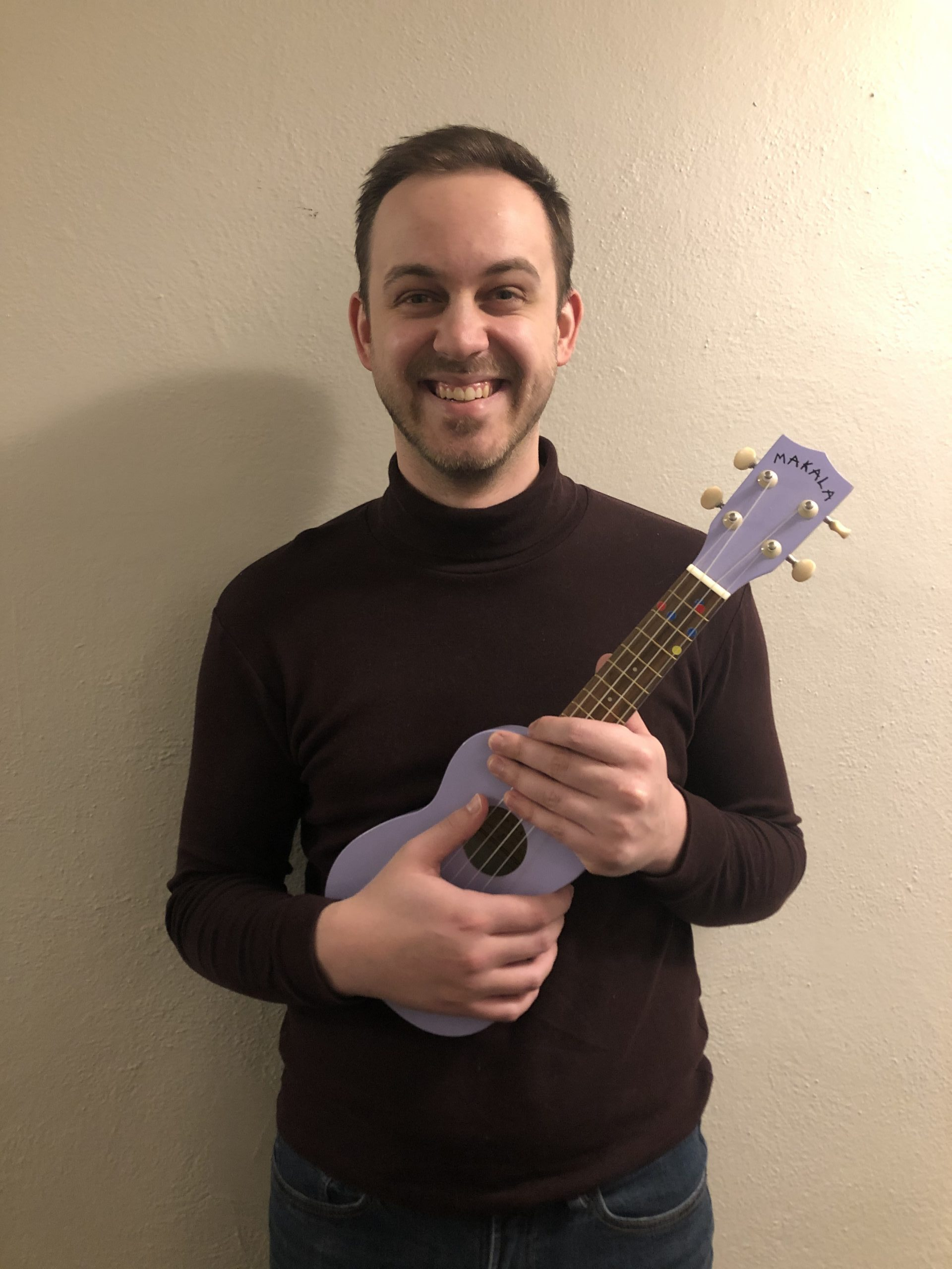 Brad smiling and holding a lilac painted ukulele.