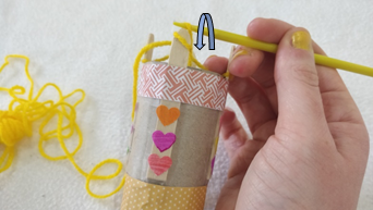 A loop of yellow yarn being pulled over another loop on the same peg of a knitting doll.