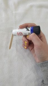 A glue stick being used on the end of a popsicle.