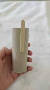 A popsicle stick glued to one side of a toilet paper tube, with the ending poking off slightly.