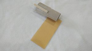 Toilet paper tube with popsicle sticks and a sheet of yellow paper underneath