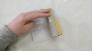 Toilet paper tube with popsicle sticks, with yellow paper rolled halfway around the tube.