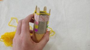 Yellow yarn wrapped around 4 pegs of a knitting doll