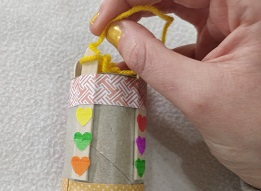 A loop of yellow yarn wrapped around a peg of a french knitting doll