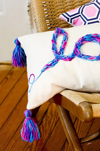 "Pillow with a french knitted piece that reads, ""love"" in cursive script."