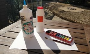 Salt, glue, paper, a paintbrush, and watercolors, sat on a table outside.