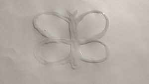 Wet glue on white paper in a butterfly shape.