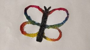 A salt butterfly painted with rainbow watercolor paints.