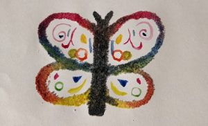 A salt butterfly colored with rainbow watercolors and rainbow shapes inside the wings.
