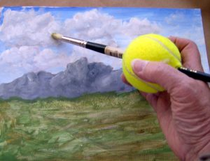 A person holding a tennis ball with a paintbrush pushed through it.