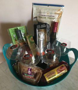A wine basket with wine, wine glasses, and snacks.