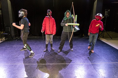 4 people onstage in homemade costumes holding fake weapons and wearing masks and helmets.