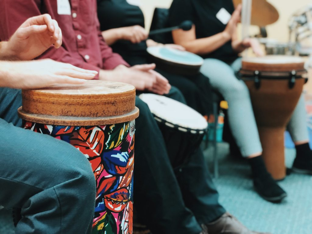 Close up of group of people playing floor drums.