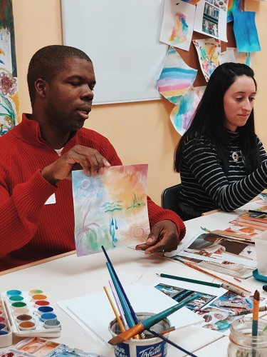 2 people sitting at an art table, one holds up a watercolor painting.