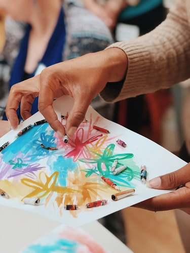 A close up of a person attaching paper beads to paper with watercolor designs.