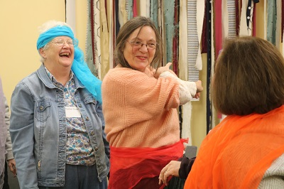 2 women wearing scarves around their heads and waists and laughing.